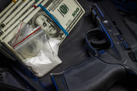 Drug in the form of white powder in plastic bags on packs of dollars with a gun