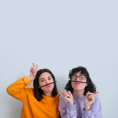 two women with pencil as mustaches