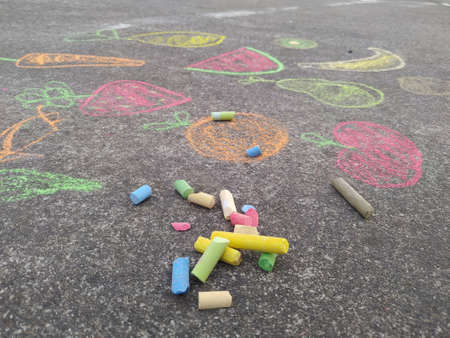 child's hand painting with colored chalk on the ground