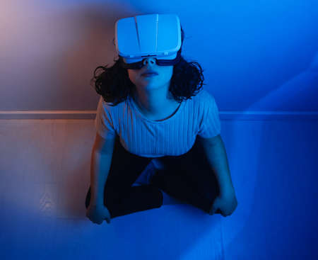 young woman sitting on the floor using virtual reality device. interior artificial light cold and warm colors. leisure activities at home.