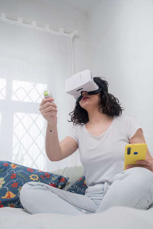 young woman with vr glasses. leisure activity at home virtual reality. I jump playing the guitar. white bedroom. Imagens