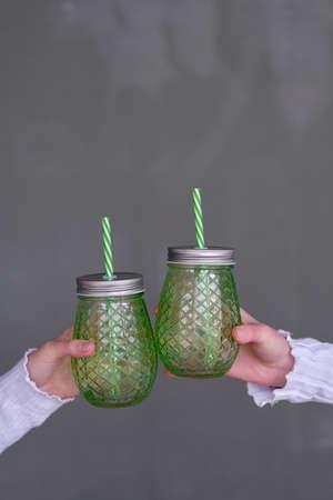 两只手拿着两个绿色的水壶,上面有吸管。清凉饮料的概念