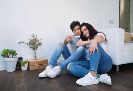 young heterosexual couple happily look at the result of a pregnancy test. they are sitting on the floor of their home. indoor natural light. fertility concept Imagens