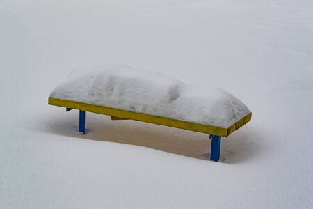 yellow bench under a large snowdrift. winter landscape Stock Photo