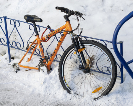 Petrozavodsk, Russia - 1 march 2019. Wheelless orange bicycle strapped to the iron fence Redakční
