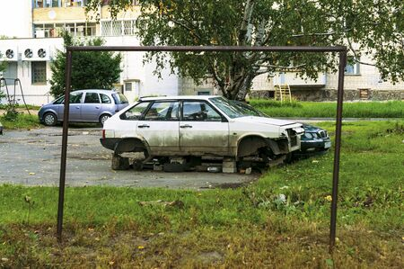 old dirty white passenger car without wheels