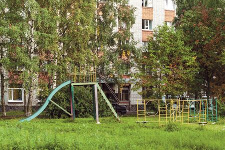 summer landscape with an old metal children s slide in a poor Russian town