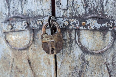 old rusty padlock closes gate. paint on the gate peeling and cracked