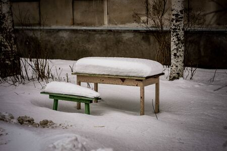 landscape with table and benches under the snow Фото со стока