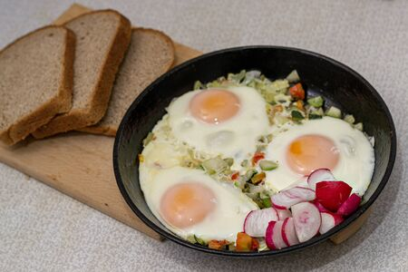 Three eggs with vegatables on frying pan and three slices of bread are on wooden board.