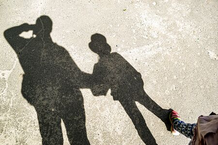 Photo of shadows of father and daughter on asphalt Фото со стока - 137183769
