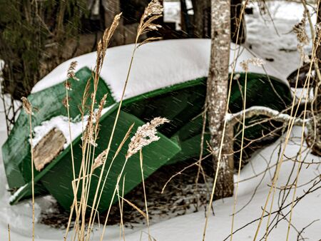 Overturned wooden boat under the snow, vessel winter storage, country landscape. Focus on foreground. Фото со стока