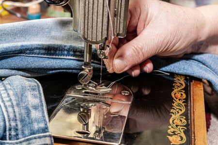 thread a needle in sewing machine and item of clothing Фото со стока - 137187533