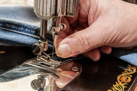 thread a needle in sewing machine and item of clothing Фото со стока