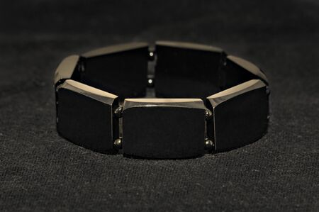 jet bracelet on black background. Low-key lighting Фото со стока