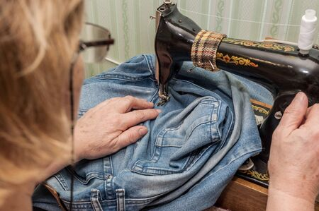 old woman in glasses working in sewing machine Фото со стока - 137187584
