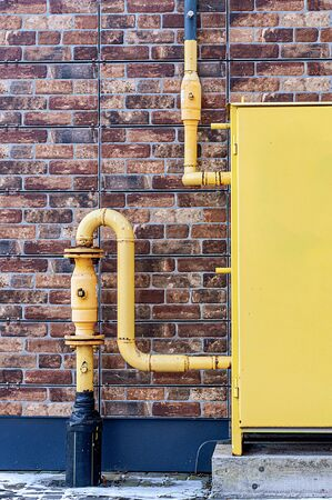yellow gas pipes on a brick wall background