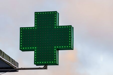 Green medical cross sign against sky in winter day Фото со стока - 137187451