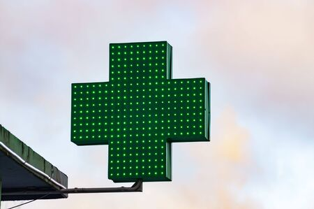 Green medical cross sign against sky in winter day