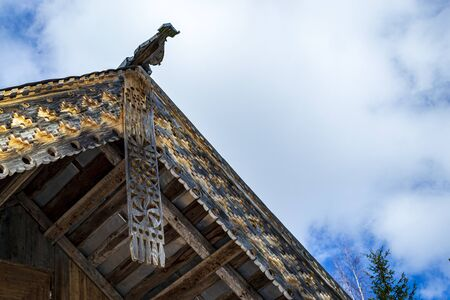 beautiful carved platbands on the roof of a wooden house and the sky with clouds