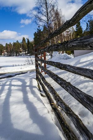 a fence made of poles and a Sunny winter landscape