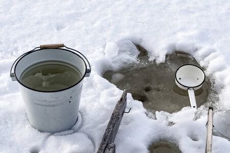 Bucket with water near the ice hole in the cold on the white snow. Фото со стока - 138096259