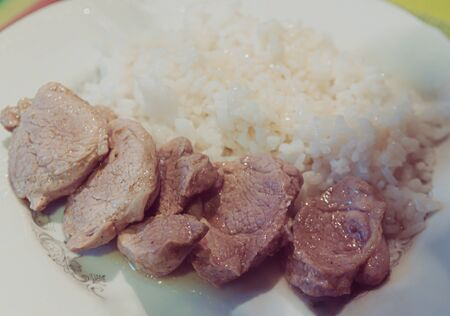 rice with pieces of meat on a white plate