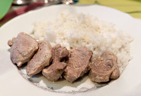 rice with pieces of meat on a white plate Фото со стока - 138092928