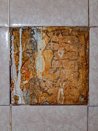 close up of falling off tiled tiles in the bathroom