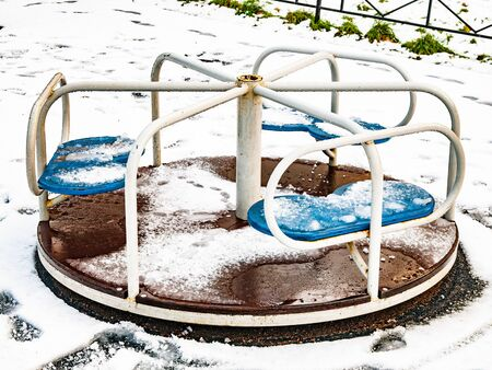Children carousel on the playground in winter day