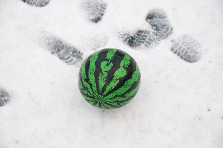 the green ball looks like a watermelon on the snow