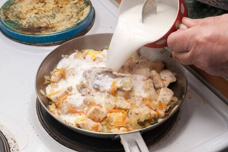 the process of cooking chicken in a creamy sauce. cream is poured into the chicken from a Cup Фото со стока - 138097184