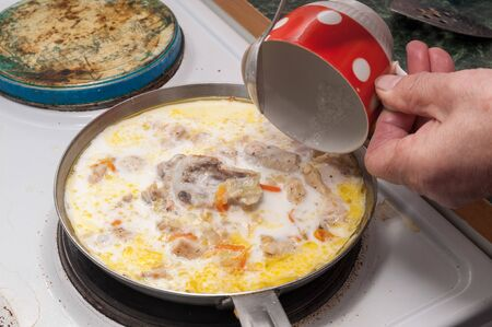 the process of cooking chicken in a creamy sauce. cream is poured into the chicken from a Cup