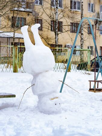 funny snowman standing on his head in winter day