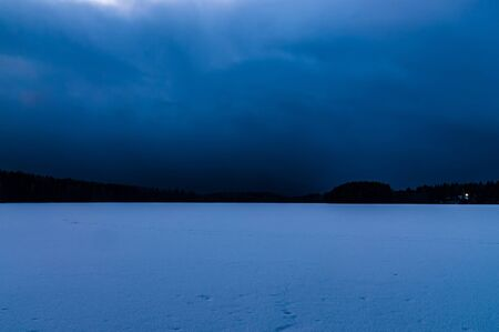 night winter landscape with a frozen lake and sky tightened clouds