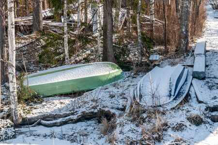 Overturned boats under the snow, vessel winter storage, country landscape.