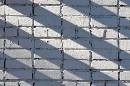 abstract background with a brick wall and diagonal shadows on it Фото со стока