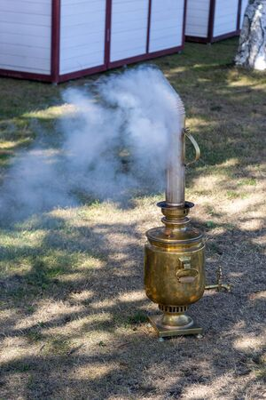 samovar standing on the ground. Smoke is coming from the chimney of the samovar. Russian culture Banque d'images