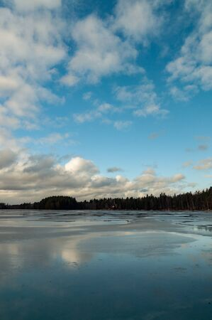 winter landscape with a frozen lake and clouds on a sunny day