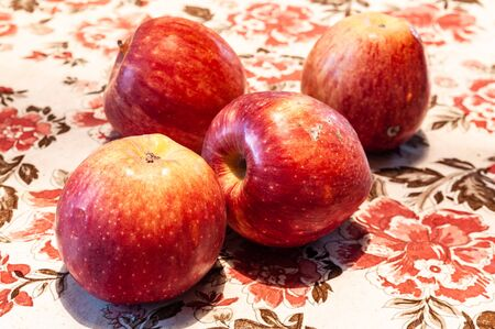 four red apples lying on the table