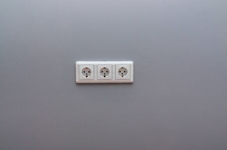 white triple socket on the gray wall.