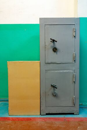 very old double safe. a closed safe against the green wall Archivio Fotografico