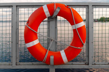 an orange lifebuoy hangs on the fence opposite the water