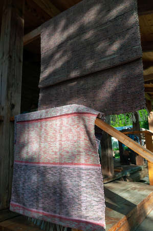 fabric rugs hang on wooden railings of the village house