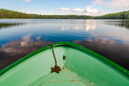 the bow of the boat and a lake with a far shore covered with forest. focus on foreground
