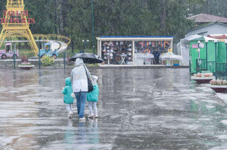 Petrozavodsk, Russia - 1 August 2020. woman with two children walking in the heavy rain in amusement park Редакционное