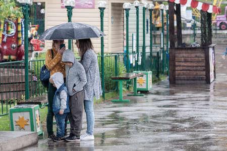 Petrozavodsk, Russia - 1 August 2020. teens and children hiding from heavy rain in amusement park Редакционное
