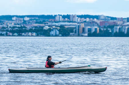 Petrozavodsk, Russia - 2 August 2020. man kayaking on a big lake against the city