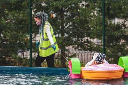 Petrozavodsk, Russia - 1 August 2020. a young woman an amusement Park worker in a protective mask pulls out a stuck boat with a child