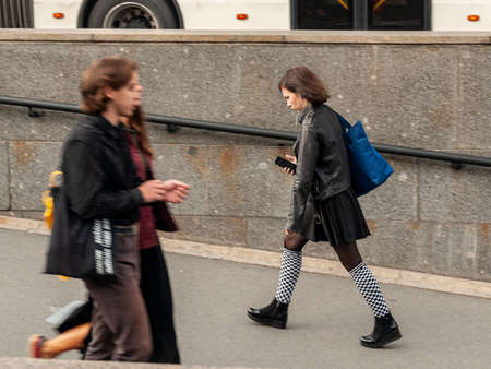 Saint Petersburg, Russia - 8 September 2020. A young girl walks quickly, looking at the phone. motion blur
